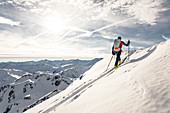 Ski tourer climbs through untouched powder snow, Alpbach valley, Tyrol, Austria
