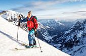 Junge Frau steigt mit Ski auf, Karwendel, Tirol, Österreich
