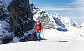Young woman on the rise with touring skis against a mighty mountain backdrop, Karwendel, Tyrol, Austria