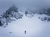 Ski tourers ascending to a steep channel with poor visibility and cloudy mountains, Wilder Kaiser, Tyrol,