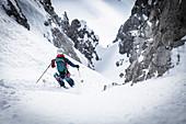 Ski alpinist descending a steep channel, Mieminger chain, Tyrol, Austria