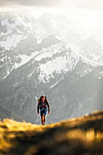 Young blonde woman in shorts hiking in wonderful warm back light with snowy mountains in the background, Hinterriss, Karwendel, Tyrol, Austria
