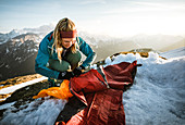 Young woman spreads her sleeping pad in the snow, Hinterriss, Karwendel, Tyrol, Austria