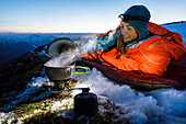 Young woman bivouacs on the summit on sleeping pad and in a bivouac sack and boils water with a gas stove, Karwendel, Tyrol, Austria