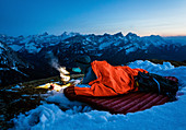 Young woman lies in her bivouac sack on a sleeping pad in the snow and boils water with a gas cooker in the glow of her headlamp in front of the Karwendel backdrop, Tyrol, Austria