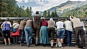 Group of people stands expectantly on a bridge in the mountains, Germany, Bavaria, Allgäu