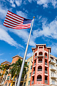 The American national flag flies in front of a colorful house facade, Naples, Florida, USA