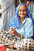 2015, Nandgoan / Nandagram, Vrindavan, Uttar Pradesh, India, Elderly woman making music at school event