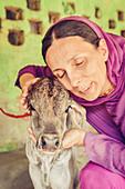 2017, Kusum Sarovara, Govardhan, Vrindavan, Uttar Pradesh, India, The priestess Nitya-Kisori devi dasi hugs a newborn cow from Udhava das Baba
