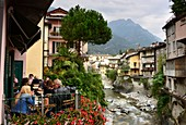 on the Mera river with cafe and medieval houses, Chiavenna, Val San Giacomo, Lombardy, Italy