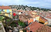 Man looks out over the rooftops of the city, on Place Saint Paul in the old town of Hyeres, Cote d'Azur, southern France