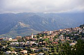 Cloudy mountains with the mountain village of Curbara in Balagne, northern Corsica, France