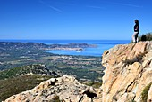 Woman looks from rocks to the bay of Calvi, Corsica, France MR present: Andrea Seifert