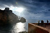 Tourists marvel at the sunset at Porto on the Gulf of Porto, western Corsica, France