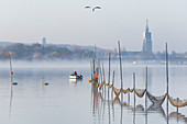 Angler on the Havel in the morning mist, Tiefer See, former Brandenburg state parliament and Heilig Geist Stift in the background, Potsdam, Brandenburg, Germany