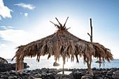 Palm umbrella on the stone beach of la Bombilla, La Palma, Canary Islands, Spain, Europe