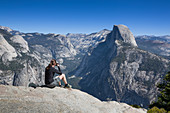 Woman photographs the Half Dome in summer with a blue sky, Yosemite National Park, USA