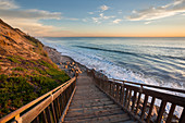 Sunset with stairs to the beach on the west coast in California