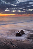 Sunset on the beach on the west coast of California with waves, USA