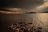 Winter sun lights Ardvreck Castle, Loch Assynt, Scotland, United Kingdom, Europe