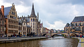 Locals and visitors relax along the Leie canal, famous for its beautiful historic facades, Graslei, Ghent, Belgium, Europe