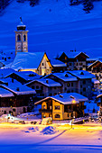 Church and houses illuminated during a winter twilight, Livigno, Valtellina, Lombardy, Italy, Europe