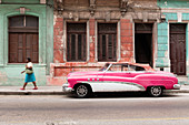 Woman walks past a pink and white vintage car, parked on street in Havana, Cuba, West Indies, Caribbean, Central America