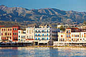View across the Venetian Harbour to colourful waterfront buildings beneath the Lefka Ori, Hania (Chania), Crete, Greek Islands, Greece, Europe