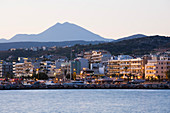 Seafront buildings illuminated at dawn, Mount Psiloritis, aka Mount Ida, in background, Rethymno (Rethymnon), Crete, Greek Islands, Greece, Europe