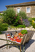 Fresh purchases like fruit and vegetables in a garden in front of a stone house, France