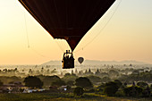 Hot air balloon over landscape with temples at sunset, Bagan, Myanmar.