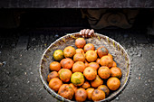 High angle close up of basket of orange citrus fruits in Myanmar.