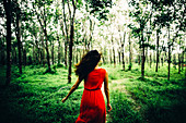 Rear view of young woman wearing red dress running in a forest.