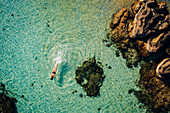 High angle view of woman swimming in the ocean in between rocks.