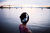 Rear view of woman with flowers in her hair, standing by the sea at sunset, bridge in the distance.