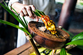 Close up of chef preparing charcoal-grilled prawn satay on a coconut shell.