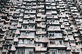 Low angle view of facade of towering residential complex with windows and balconies.