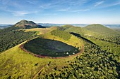 France, Puy de Dome, area listed as World Heritage by UNESCO, the Regional Natural Park of the Volcanoes of Auvergne, Chaine des Puys, Orcines, the crater of Puy Pariou volcano, the Puy de Dome volcano in the background (aerial view)