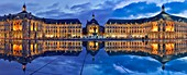 France, Gironde, Bordeaux, area listed as World Heritage by UNESCO, Bourse Place, La Lune harbour, night view of a historic building and its reflection on water esplanade