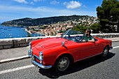 "France, Alpes Maritimes, Villefranche sur Mer, collection convertible Alfa Romeo Giulietta on the Basse Corniche road overlooking the city (Compulsory mention: Company ""Rent a Classic Car"")"