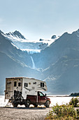 Camper, motorhome pauses on the coast in Haines, Alaska. Glacier is melting in the background