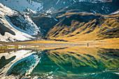 Wanderer und Bündner Berglandschaft spiegeln sich im Bergsee, Lai da Rims, Graubünden, Schweiz, Europa