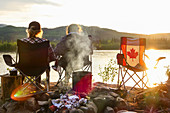 Two girls sit by the fire in the sunset and enjoy the view of the Yukon River. Canada, Whitehorse, Yukon
