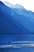 Kayakers in the sea against a mountain backdrop. Heines, Alaska,