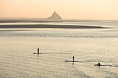 France, Manche, Mont Saint Michel bay, listed as World Heritage by UNESCO, a kayakists riding the Mascaret wave during fall high tides