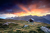 Wooden hut under fiery sky and clouds at sunset, Muottas Muragl, St. Moritz, Canton of Graubunden, Engadine, Switzerland, Europe