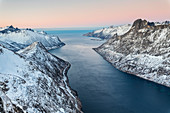 Top view of the snowy peaks surrounding Fjordgard framed by the frozen sea at sunset, Ornfjorden, Senja, Troms, Norway, Scandinavia, Europe