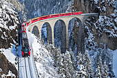 The red train of the Albula-Bernina Express Railway, UNESCO World Heritage on the Landwasser Viaduct, Switzerland, Europe