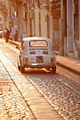 Fiat 500 driving down cobbled street, Noto, Sicily, Italy, Europe