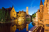 Reflection in canal of Belfort (belfry tower) illuminated at night, Old Town, UNESCO World Heritage Site, Bruges, Flanders, Belgium, Europe